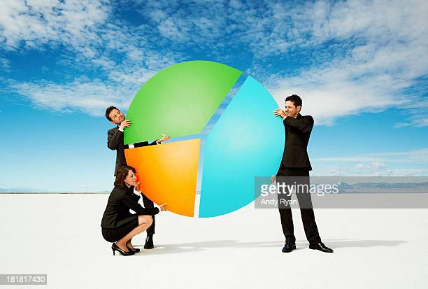 Businesspeople holding giant pie chart in desert.