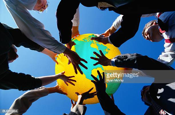 Businesspeople Holding Up a Globe
