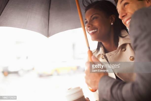 Businesspeople huddled under umbrella