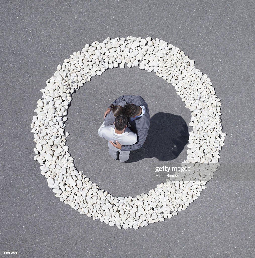 Businesspeople huddling inside rock circle