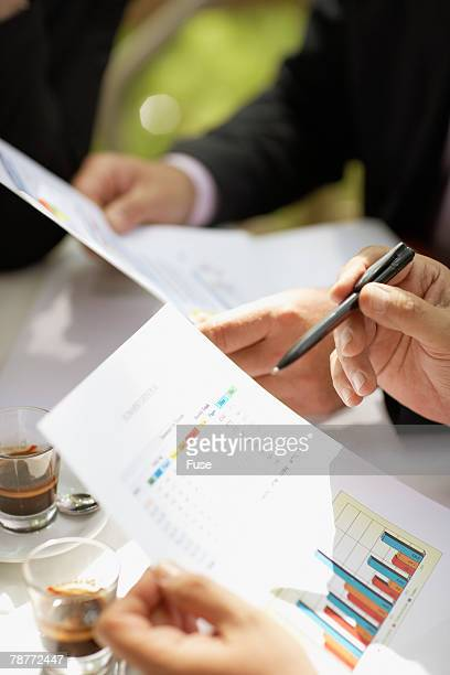 Businesspeople in a Cafe Discussing Report