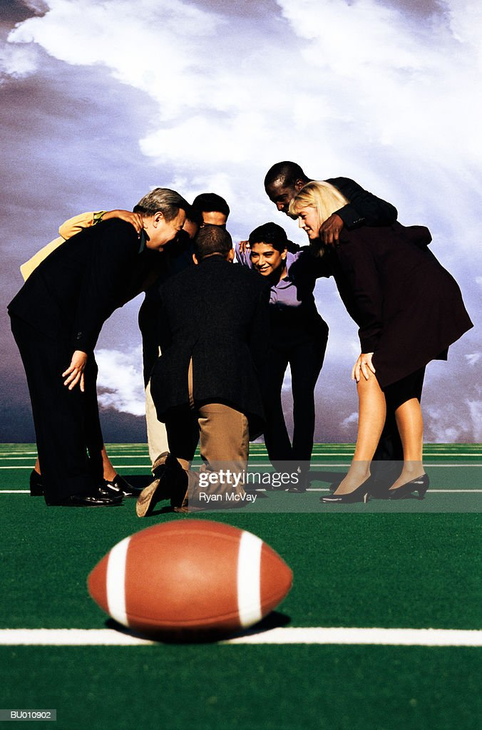 Businesspeople in a Huddle on a Football Field : Stock Photo