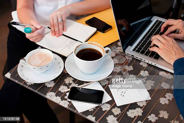 Businesspeople in cafe, man using laptop woman writing