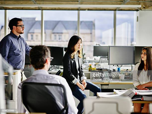 Businesspeople in discussion at workstation