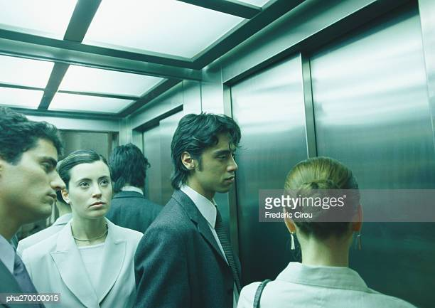 Businesspeople in elevator, head and shoulders