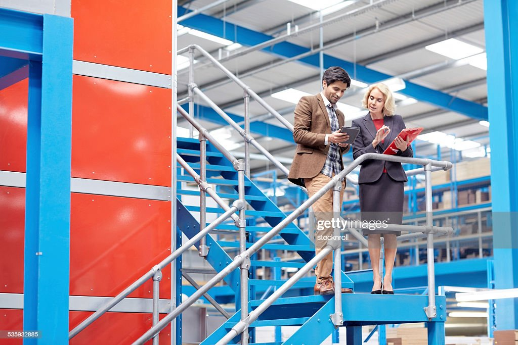 Businesspeople in factory working on digital tablet : Stock Photo