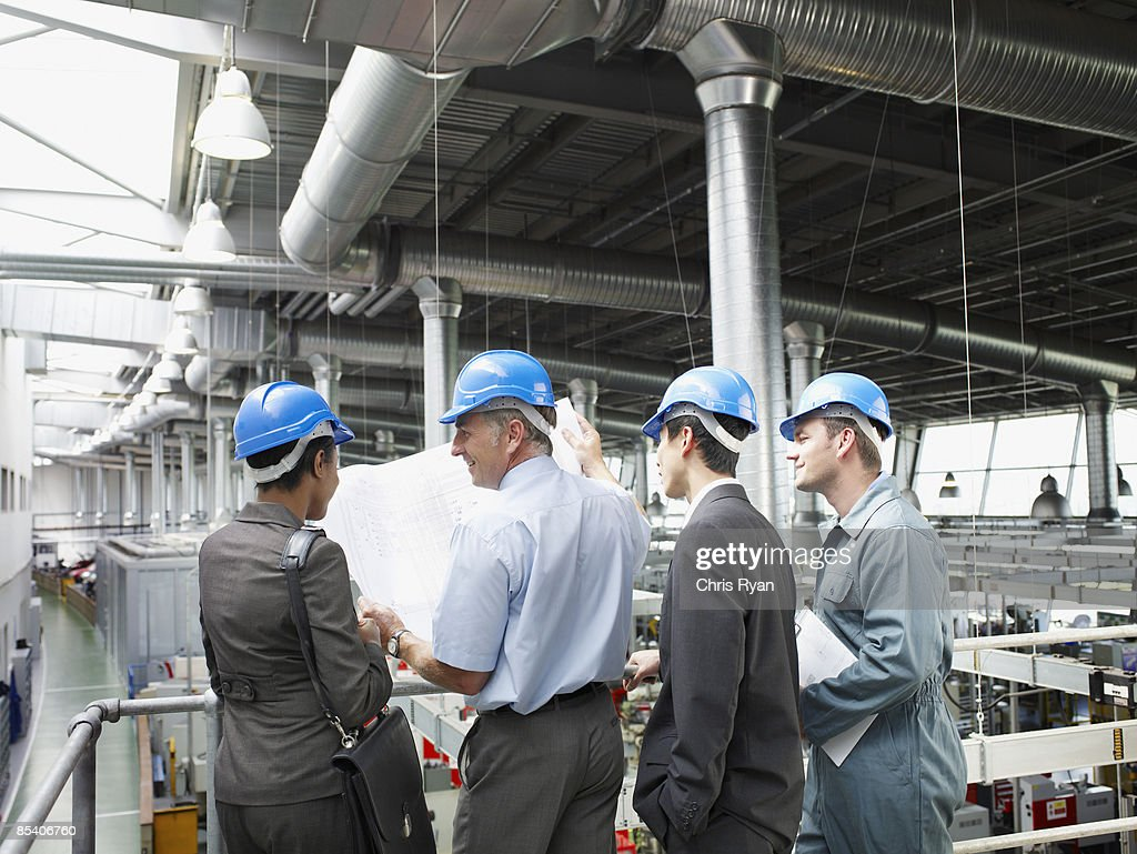 Businesspeople in hard-hats looking at blueprints : Stock Photo
