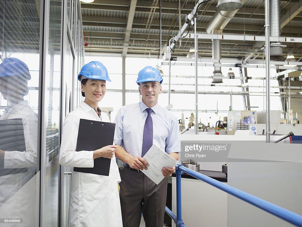 Businesspeople in hard-hats on balcony : Stock Photo