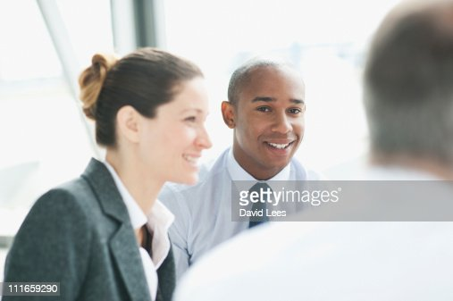 Businesspeople in meeting, smiling : Stock Photo