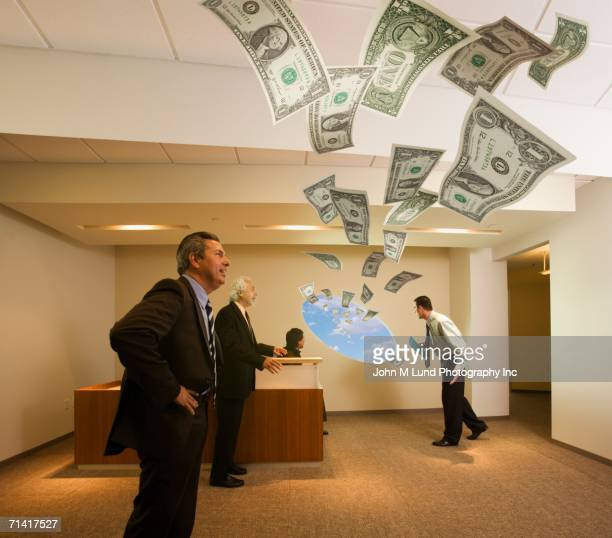 Businesspeople in office with money flying through the window
