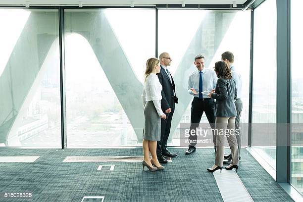 Businesspeople in office with woman using digital tablet