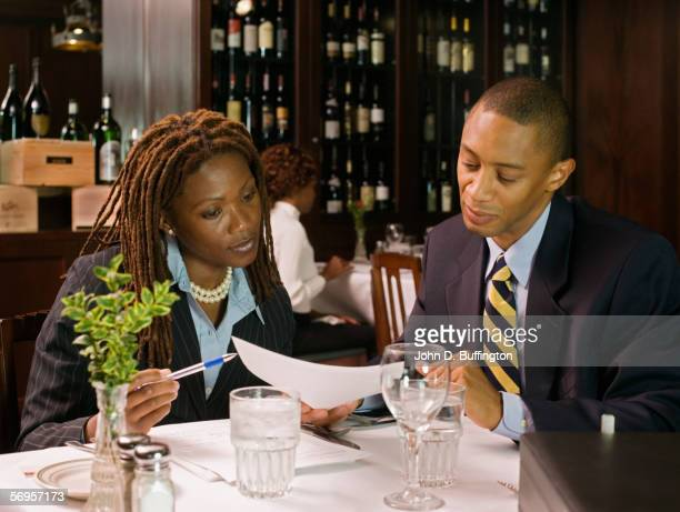 Businesspeople in restaurant looking at paperwork