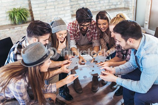 Businesspeople joining puzzle pieces in office : Stock Photo