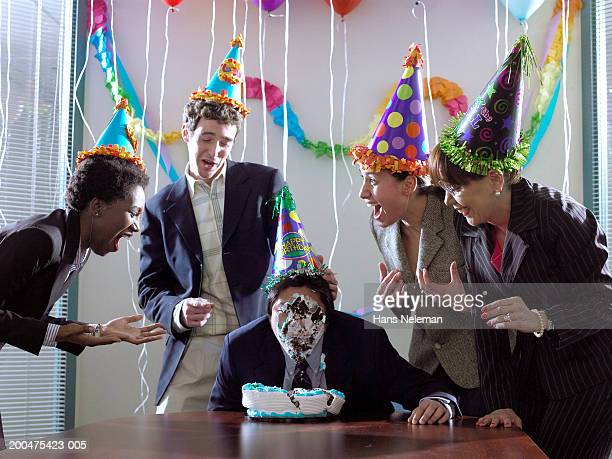 Businesspeople laughing at man with birthdaycake on face