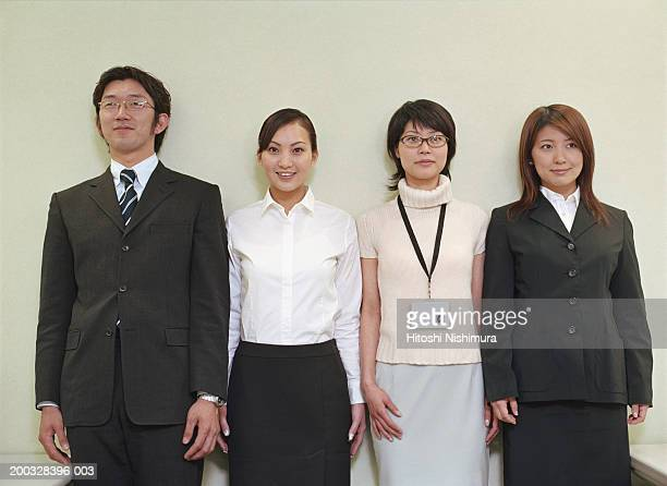 Businesspeople leaning by wall, smiling