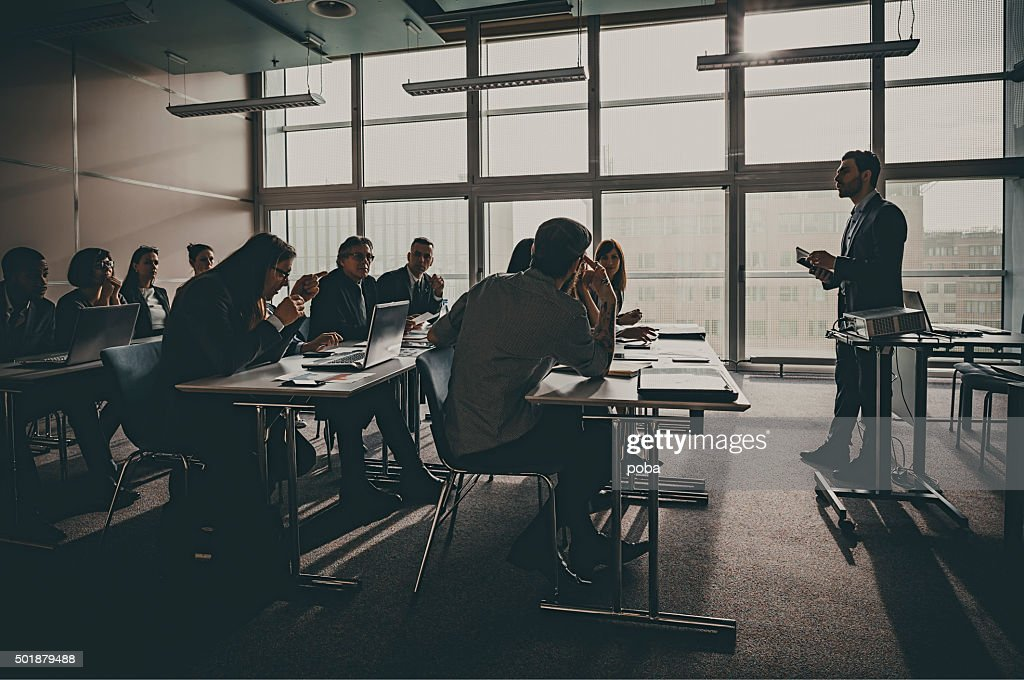 Businesspeople listening to presentation in office building : Stock Photo