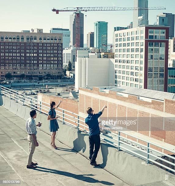 Businesspeople looking and pointing at buildings on roof terrace, Los Angeles, California, USA