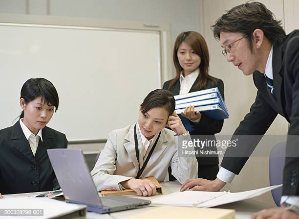 Businesspeople looking at laptop in office