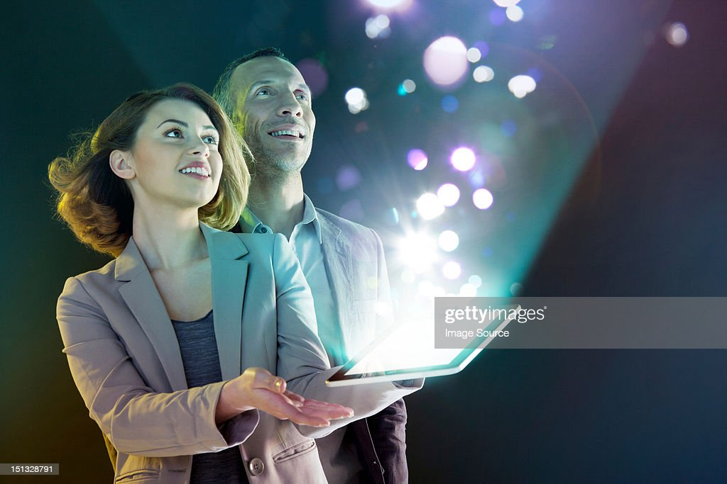 Businesspeople looking at lights coming from digital tablet