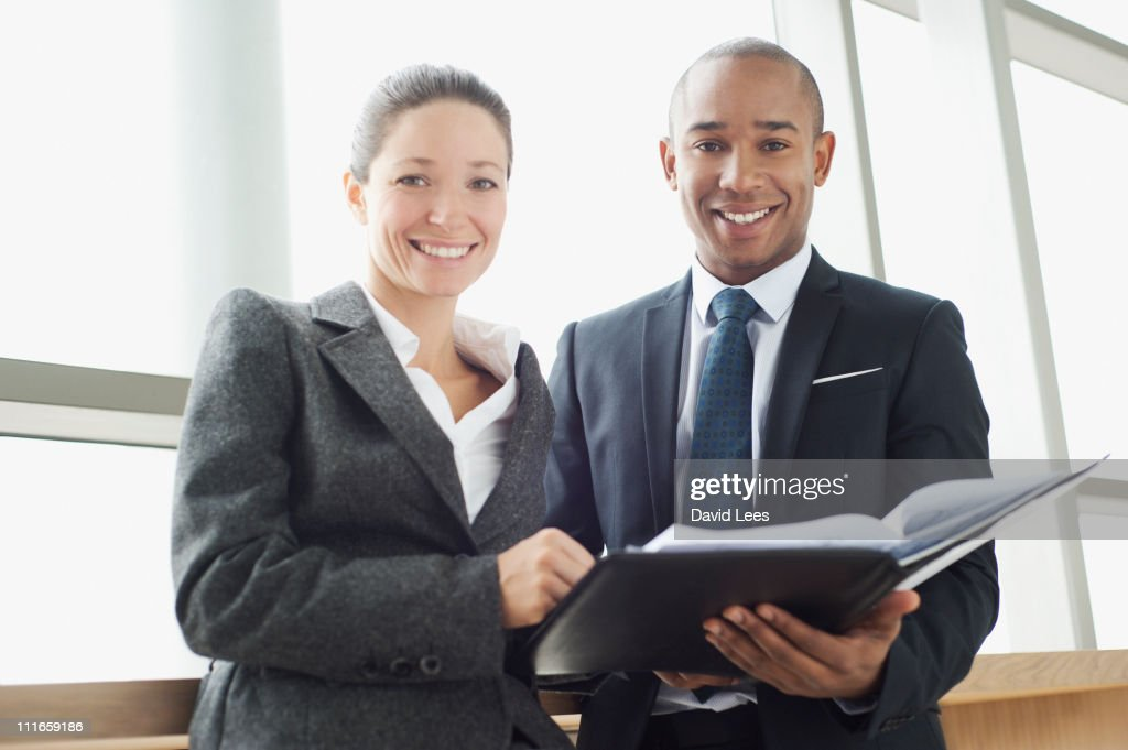Businesspeople looking at paperwork, smiling : Stock Photo