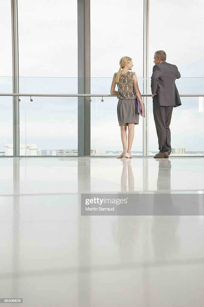 Businesspeople looking out lobby window : Stock Photo