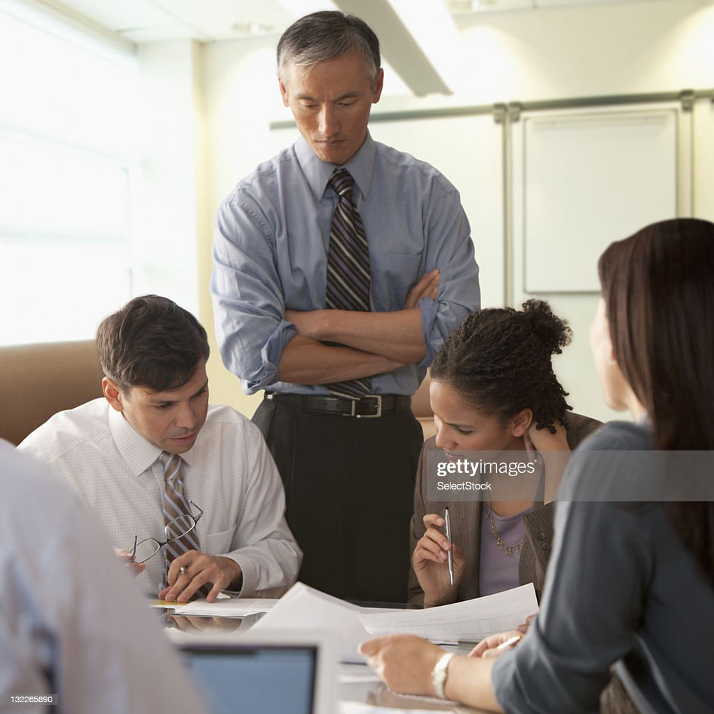Businesspeople looking over reports : Stock Photo