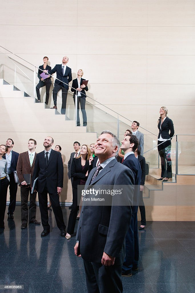 Businesspeople looking up in office lobby : Stock Photo