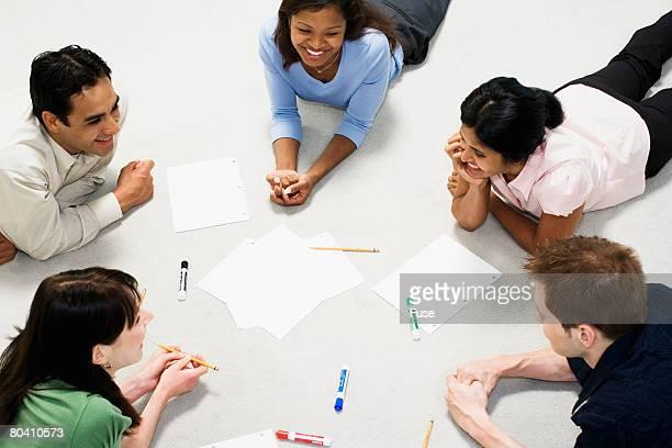 Businesspeople Lying of Floor During Meeting