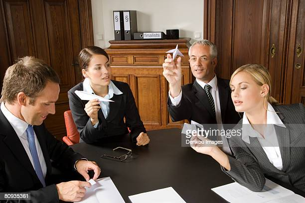 Businesspeople making paper airplanes