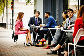 Businesspeople meeting at outdoor table of cafe