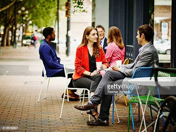 Businesspeople meeting at outdoor tables of cafe