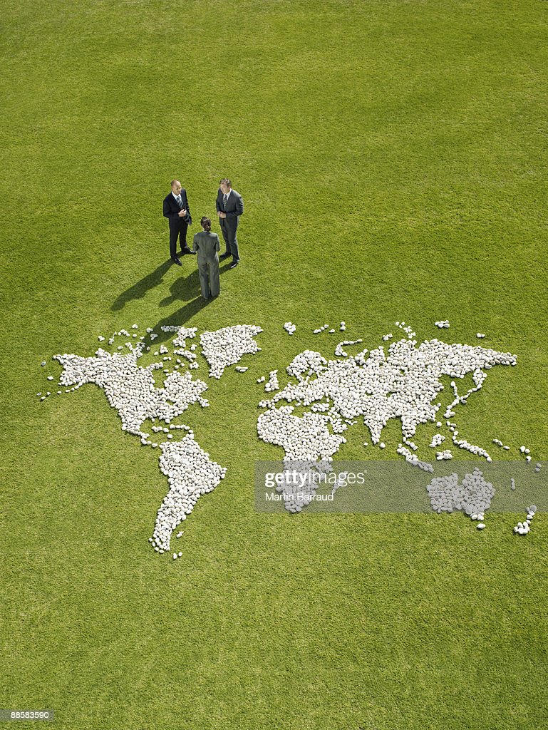 Businesspeople meeting near world map made of rocks : Stock Photo