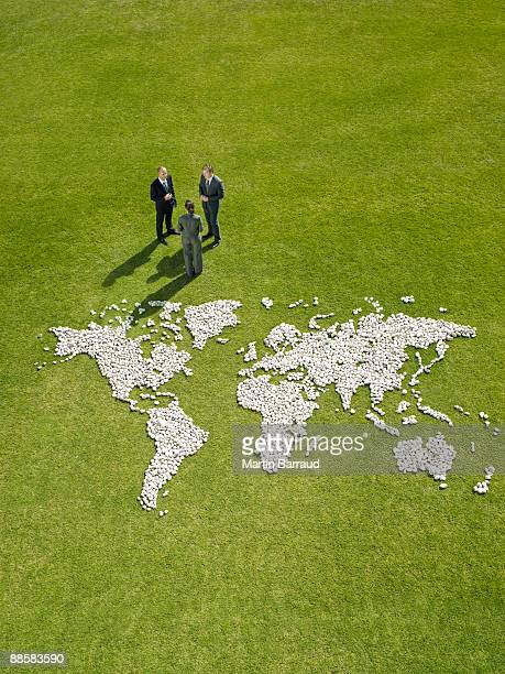 Businesspeople meeting near world map made of rocks