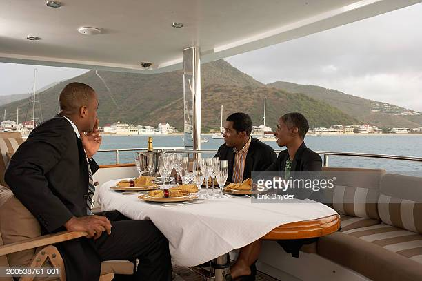 Businesspeople meeting over meal on deck of yacht