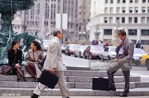 Businesspeople near outdoor fountain