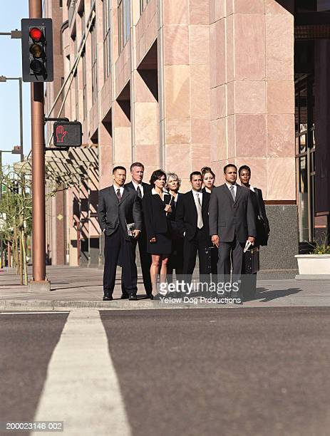 Businesspeople on curb waiting to cross street