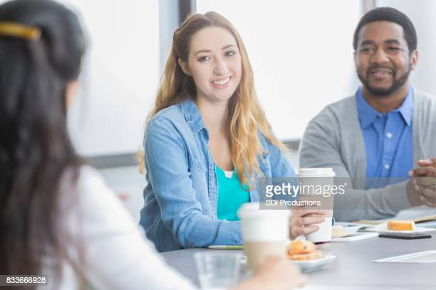 Businesspeople participate in morning staff meeting