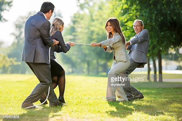 Businesspeople playing tug of war outdoors.