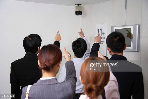 Businesspeople Pointing to CCTV Camera