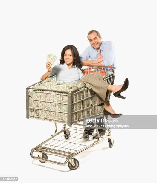 Businesspeople pushing shopping cart full of money