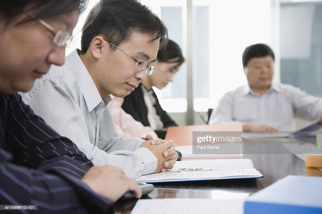 Businesspeople reading documents in conference room : Stock Photo
