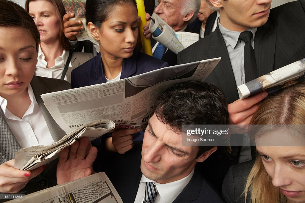 Businesspeople reading newspapers on crowded train : Photo
