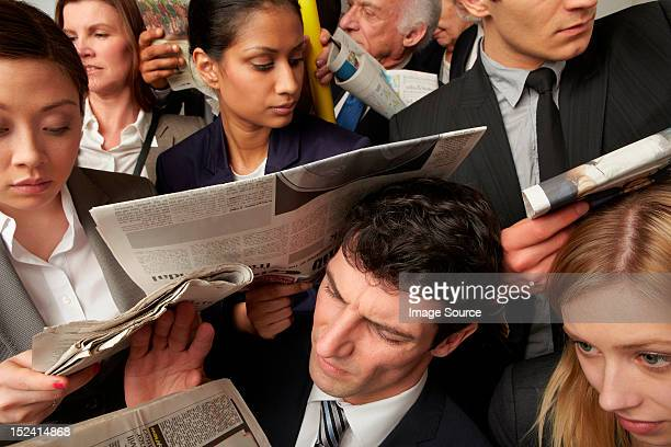 Businesspeople reading newspapers on crowded train