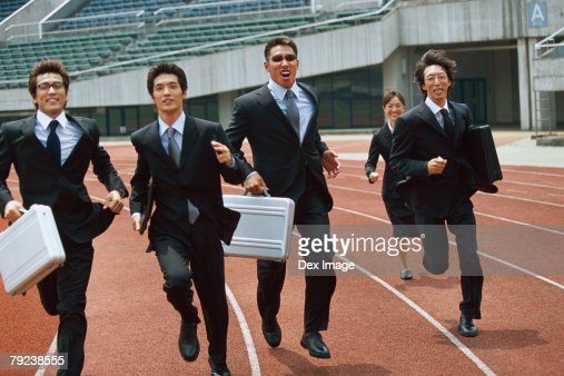 Businesspeople running on stadium track, carrying briefcases : Stock Photo