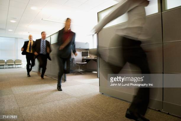Businesspeople running past office cubicles