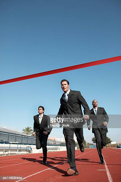businesspeople running towards finish line low angle view