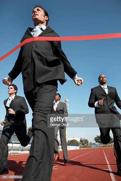 businesspeople running towards finish line, low angle view
