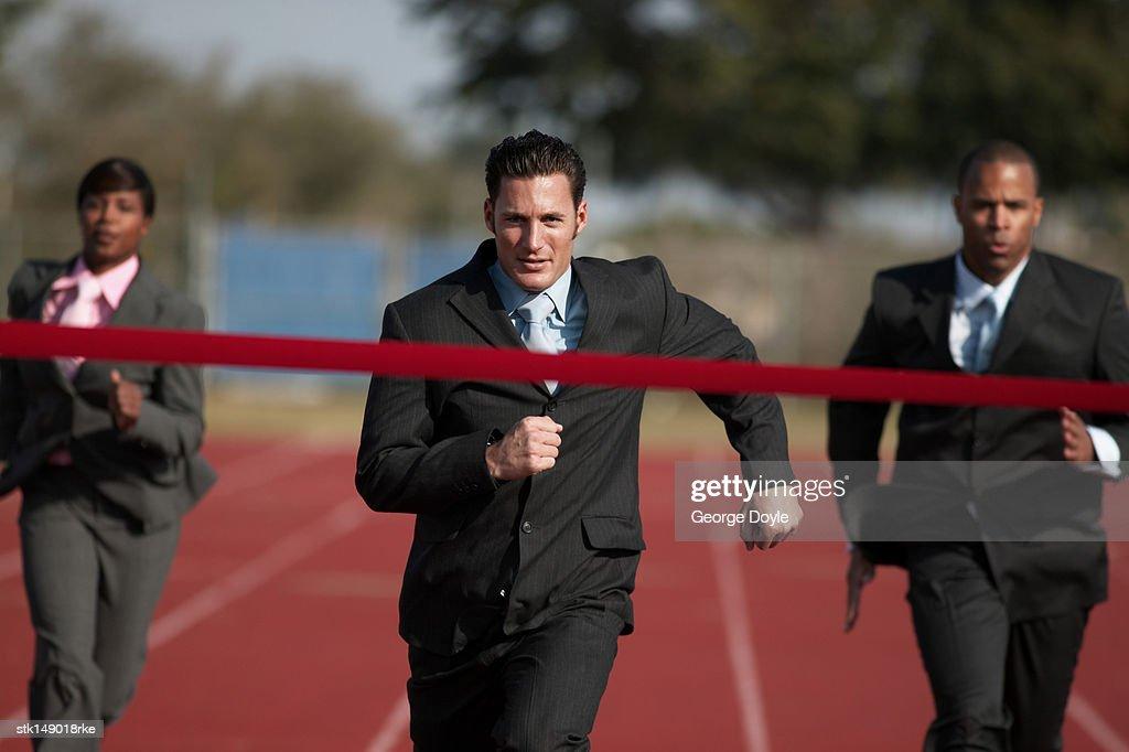 businesspeople running towards finish line : Stock Photo