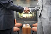 Businesspeople shaking hands in cafe