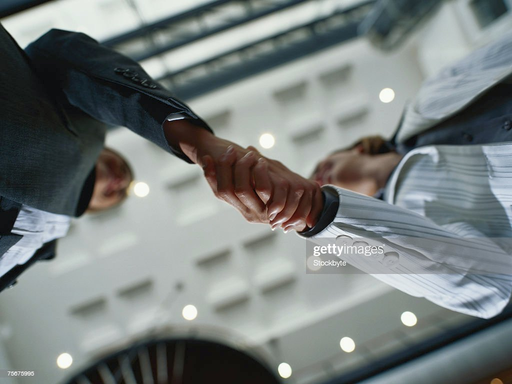 Businesspeople shaking hands, low angle view : Stock Photo